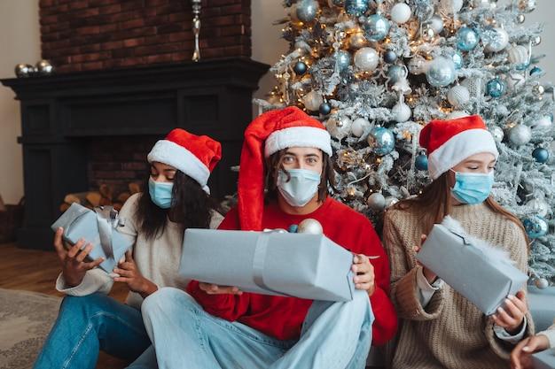 Groep vrienden in santahoeden met giften in handen