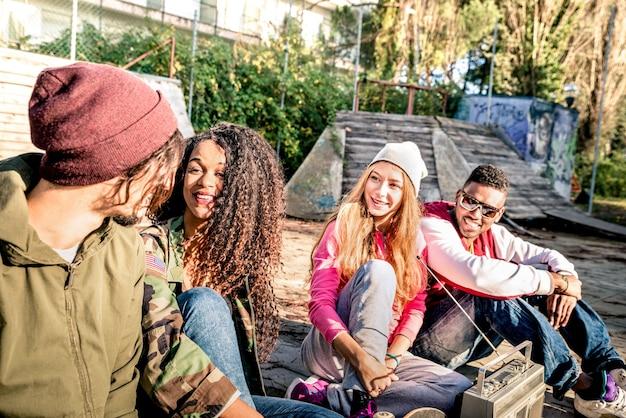 Groep vrienden in stedelijke stijl die een leuke time-out hebben in skate bmx park