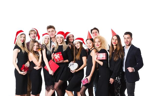 Groep vrienden in zwarte klassieke kleding met geschenken en kerstmutsen