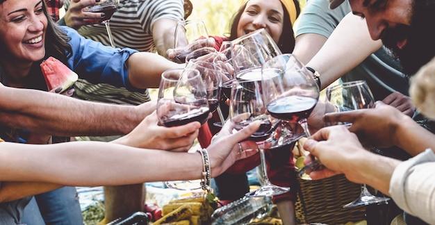 Groep vrienden juichen en roosteren met rode wijnglazen op feestje