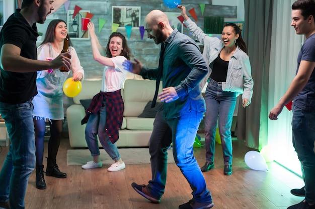 Groep vrienden juichen terwijl knappe man robotbewegingen doet op het feest.