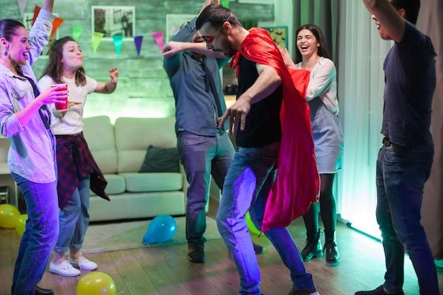 Groep vrienden juichen voor hun vriend verkleed als een superheld op het feest met rode cape.