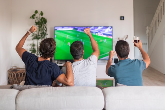 Groep vrienden kijken naar een wedstrijd op tv en vieren de overwinning van hun team