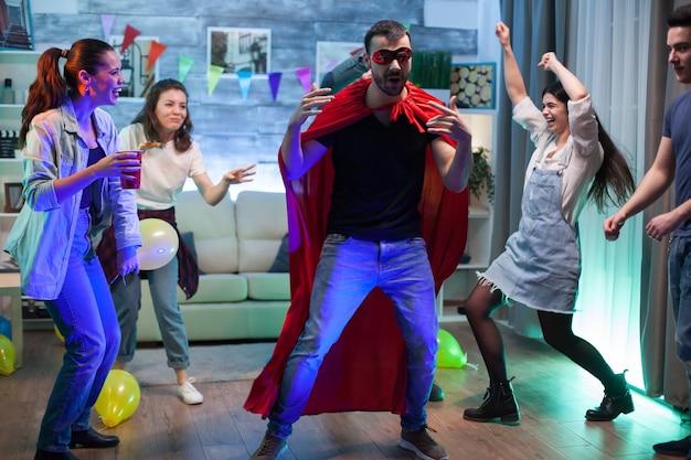 Groep vrienden kijken naar jonge man gekleed in superheld kostuum op feestje.