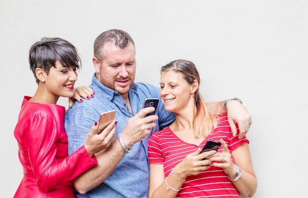 Groep vrienden kijken naar slimme mobiele telefoons