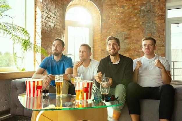 Groep vrienden kijken naar spel op tv thuis. sportfans brengen samen tijd door en hebben plezier