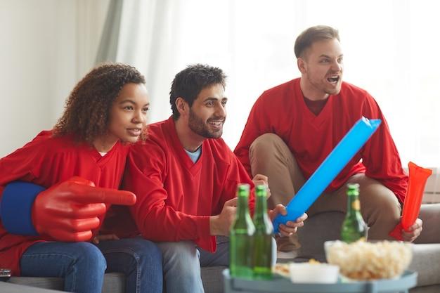 Groep vrienden kijken naar sportwedstrijd op tv thuis en emotioneel juichen terwijl ze rode teamuniformen dragen