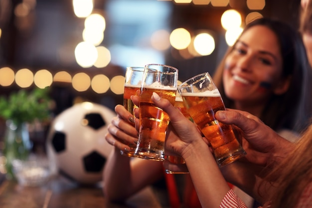 Groep vrienden kijken naar voetbalwedstrijd in pub