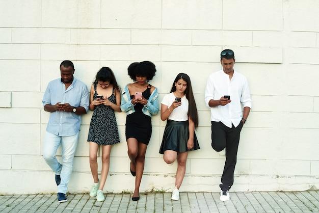 Groep vrienden lachen om iets dat ze smartphone bekijken.