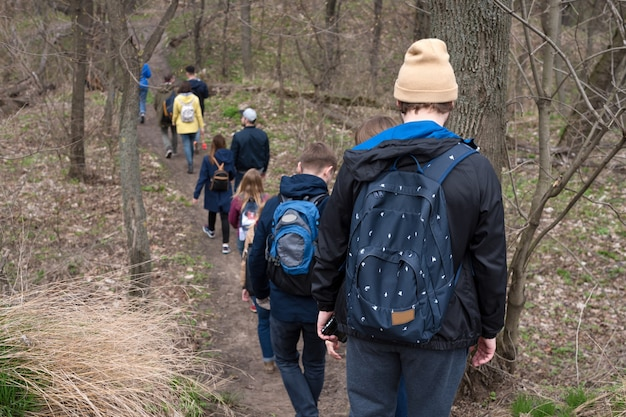 Groep vrienden lopen met rugzakken in het bos van de lente van achteren