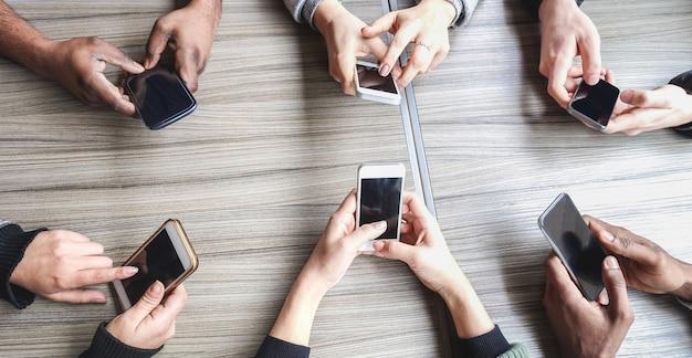 Groep vrienden met behulp van smartphone. mensenhanden bekijken plezier met mobiele telefoons
