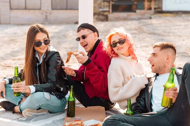 Groep vrienden met bier en pizza die pret hebben die in openlucht zitten