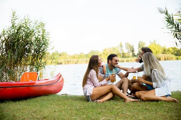 Groep vrienden met ciderflessen die door de boot dichtbij het mooie meer zitten en pret hebben