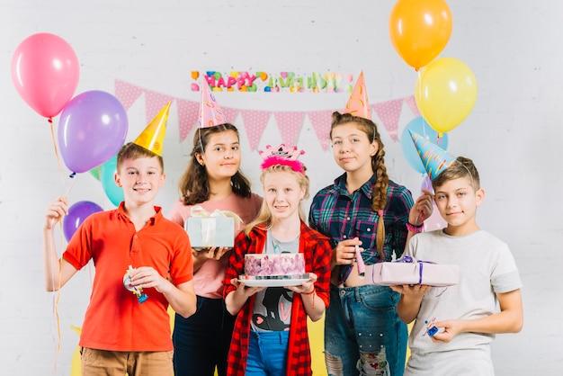 Groep vrienden met de verjaardagscake van de meisjesholding