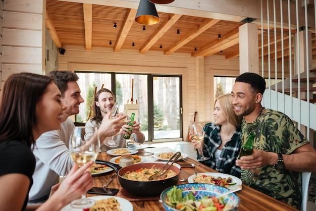 Groep vrienden met diner en lachen aan de tafel