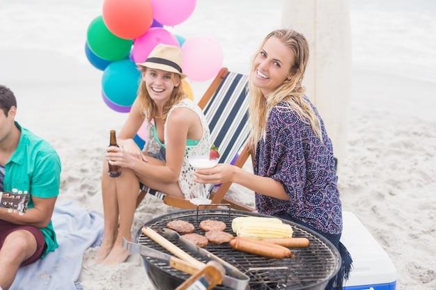 Groep vrienden met dranken die naast een barbecue zitten
