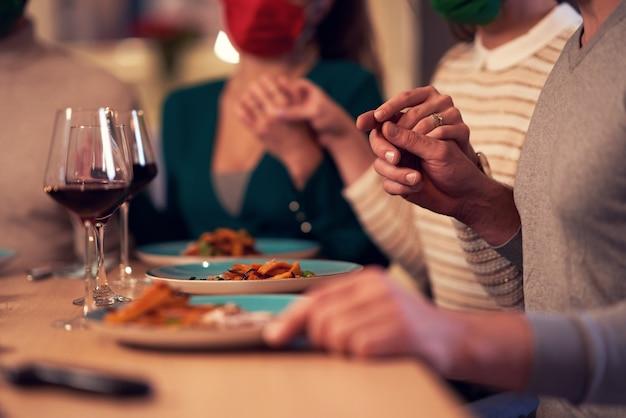 Groep vrienden met maskers die thuis bidden boven thanksgiving-kersttafel table