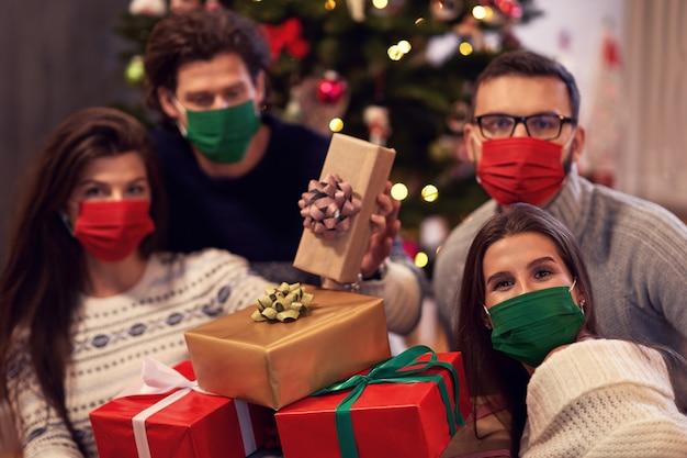 Groep vrienden met maskers die thuis kerstcadeautjes uitwisselen Premium Foto