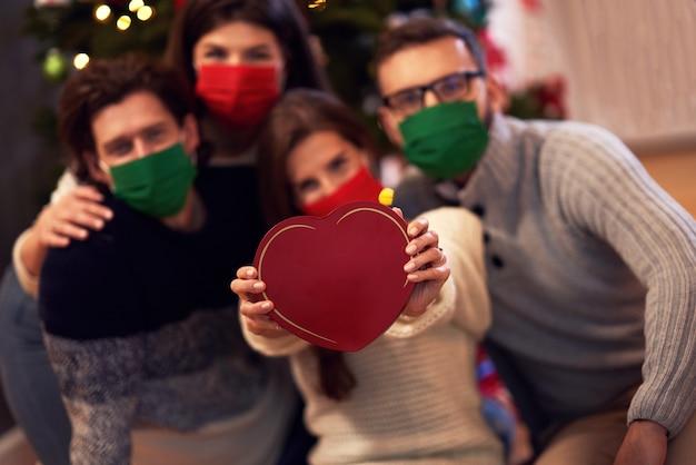 Groep vrienden met maskers die thuis kerstcadeautjes uitwisselen