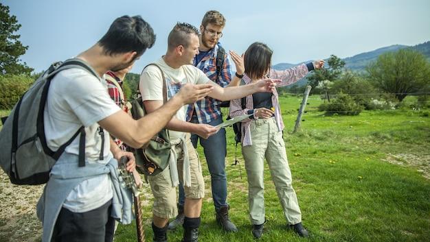 Groep vrienden met rugzakken die de kaart controleren en ergens wijzen