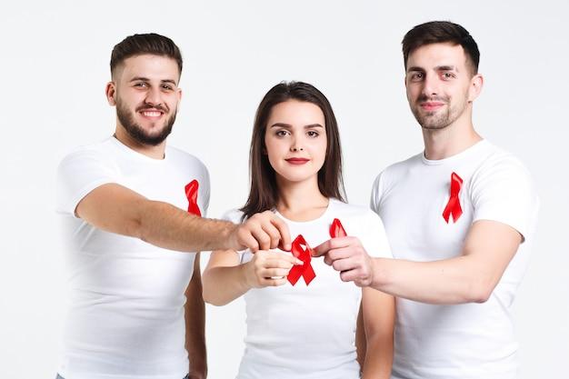 Groep vrienden met waterverf van rood lint. de dagconcept van aids van de wereld. op de witte achtergrond