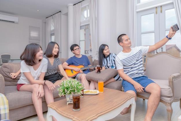 Groep vrienden nemen foto met smartphone en lied zingen met gitaar