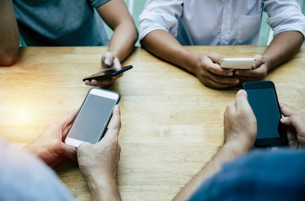 Groep vrienden of jonge mensenhanden die slimme telefoon met behulp van die sociaal voorzien van een netwerk spelen