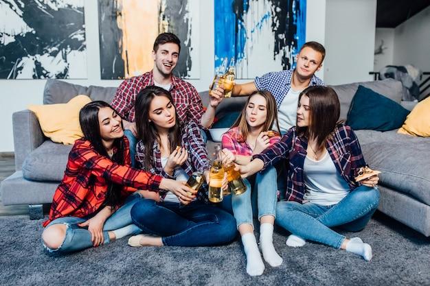 Groep vrienden ontspannen met bier en een goede tijd in het appartement.