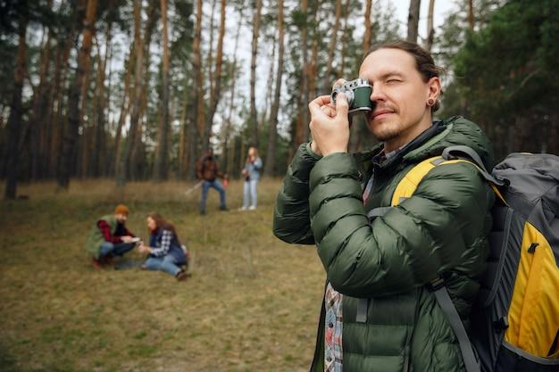 Groep vrienden op een kampeer- of wandeltocht in de herfstdag. mannen en vrouwen met toeristische rugzakken die door het bos gaan