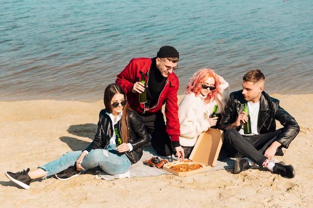 Groep vrienden op picknick bij kust