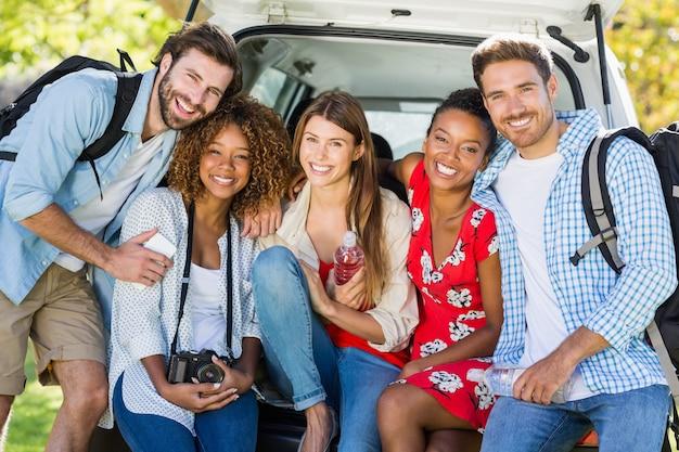 Groep vrienden op reiszitting in boomstam van auto