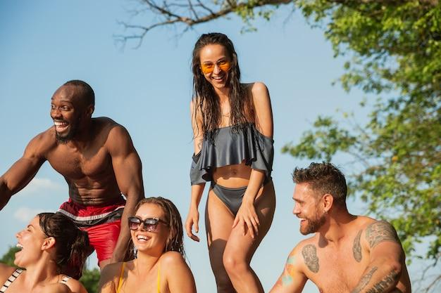 Groep vrienden opspattend water en laughting op de pier op de rivier