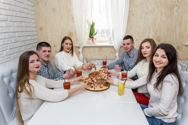 Groep vrienden pizza eten in café en poseren op camera