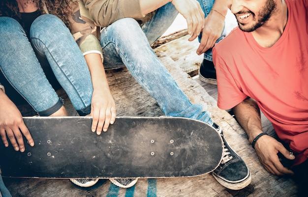 Groep vrienden plezier hebben en tijd samen doorbrengen in skateboard park