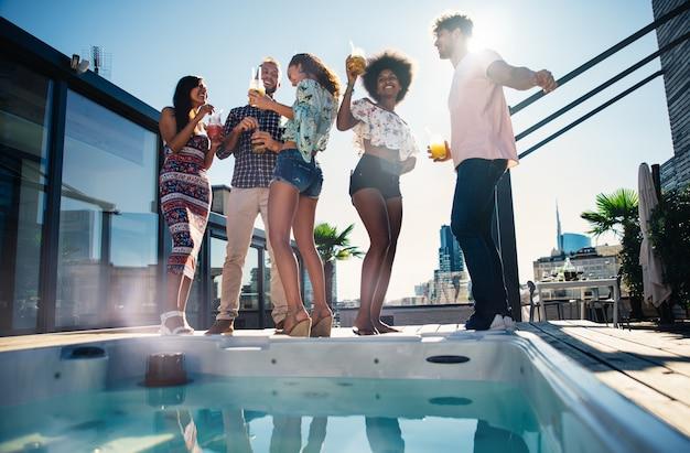 Groep vrienden plezier op het dak van een prachtig penthouse