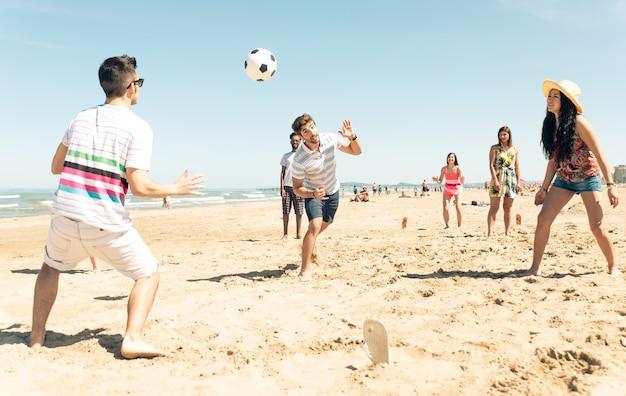 Groep vrienden plezier op het strand voetballen