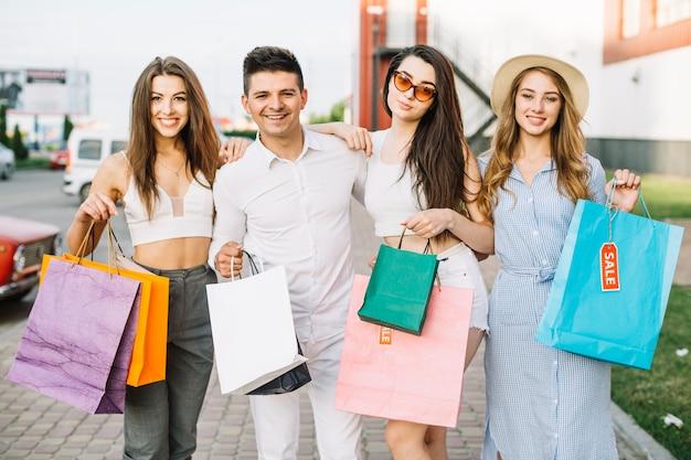 Groep vrienden poseren met papieren zakken
