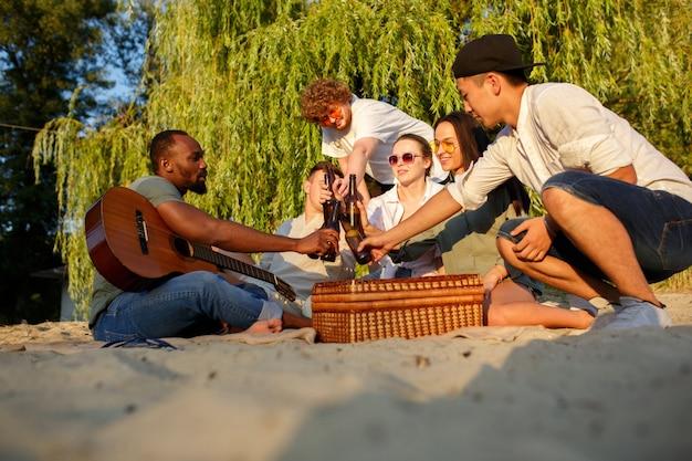 Groep vrienden rammelende bierglazen tijdens picknick op het strand