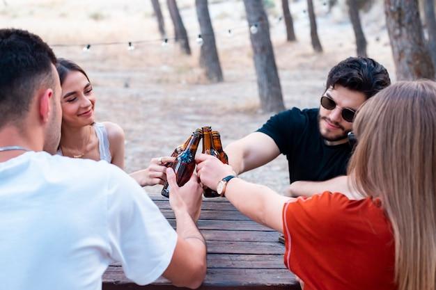 Groep vrienden roosteren met bier op een picknickplaats