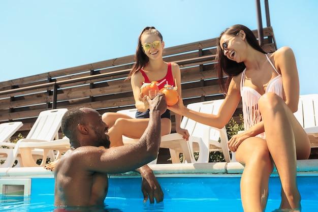 Groep vrienden spelen en ontspannen in een zwembad tijdens de zomervakantie