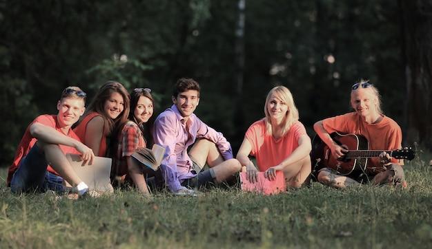 Groep vrienden studenten met boeken en gitaar zittend op het gras in het park.