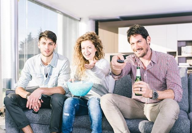 Groep vrienden televisie kijken in de woonkamer