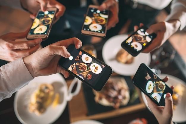 Groep vrienden uitgaan en het nemen van een foto van voedsel samen met de mobiele telefoon
