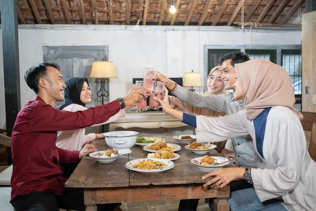 Groep vrienden vieren en heffen glazen fruitijs voor toast wanneer ze samen vasten