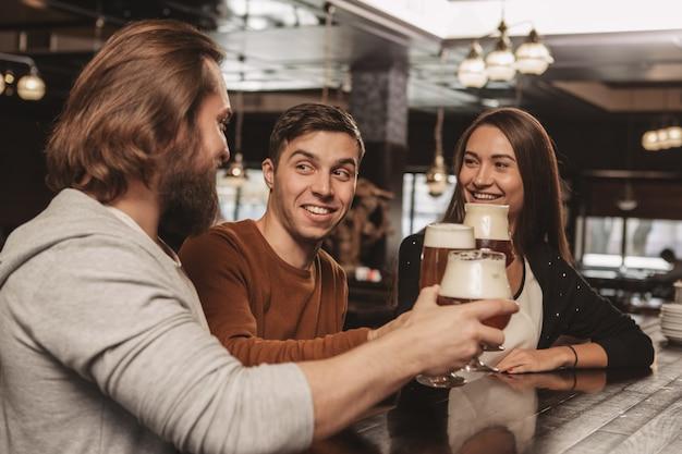 Groep vrienden vieren in de kroeg, bier drinken samen
