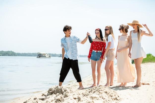 Groep vrienden vieren op het strand