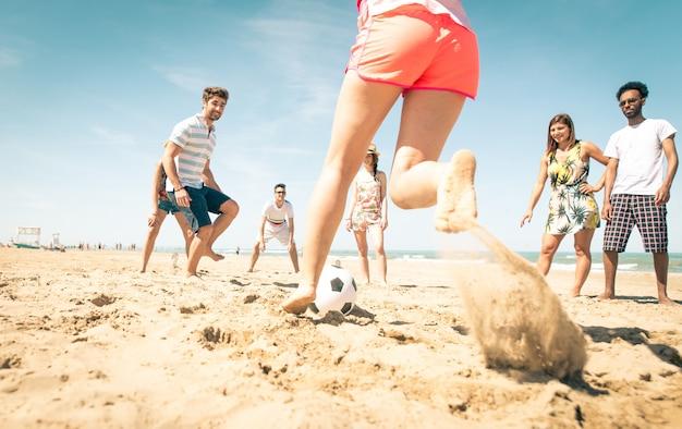 Groep vrienden voetballen op het strand