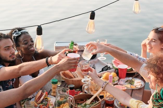 Groep vrienden zitten aan de eettafel en roosteren met cocktails die ze de vakantie buiten op een pier vieren