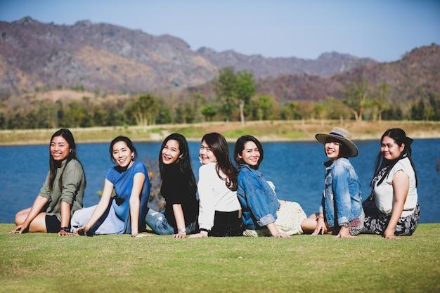 Groep vrienden zitten gelukkig samen in de buurt van het meer
