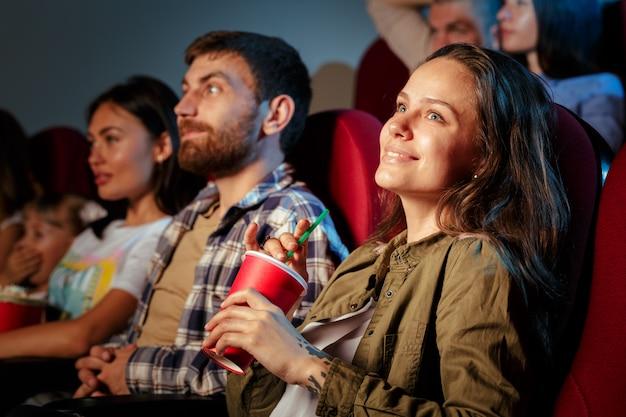 Groep vrienden zitten in de bioscoop met popcorn en drankjes